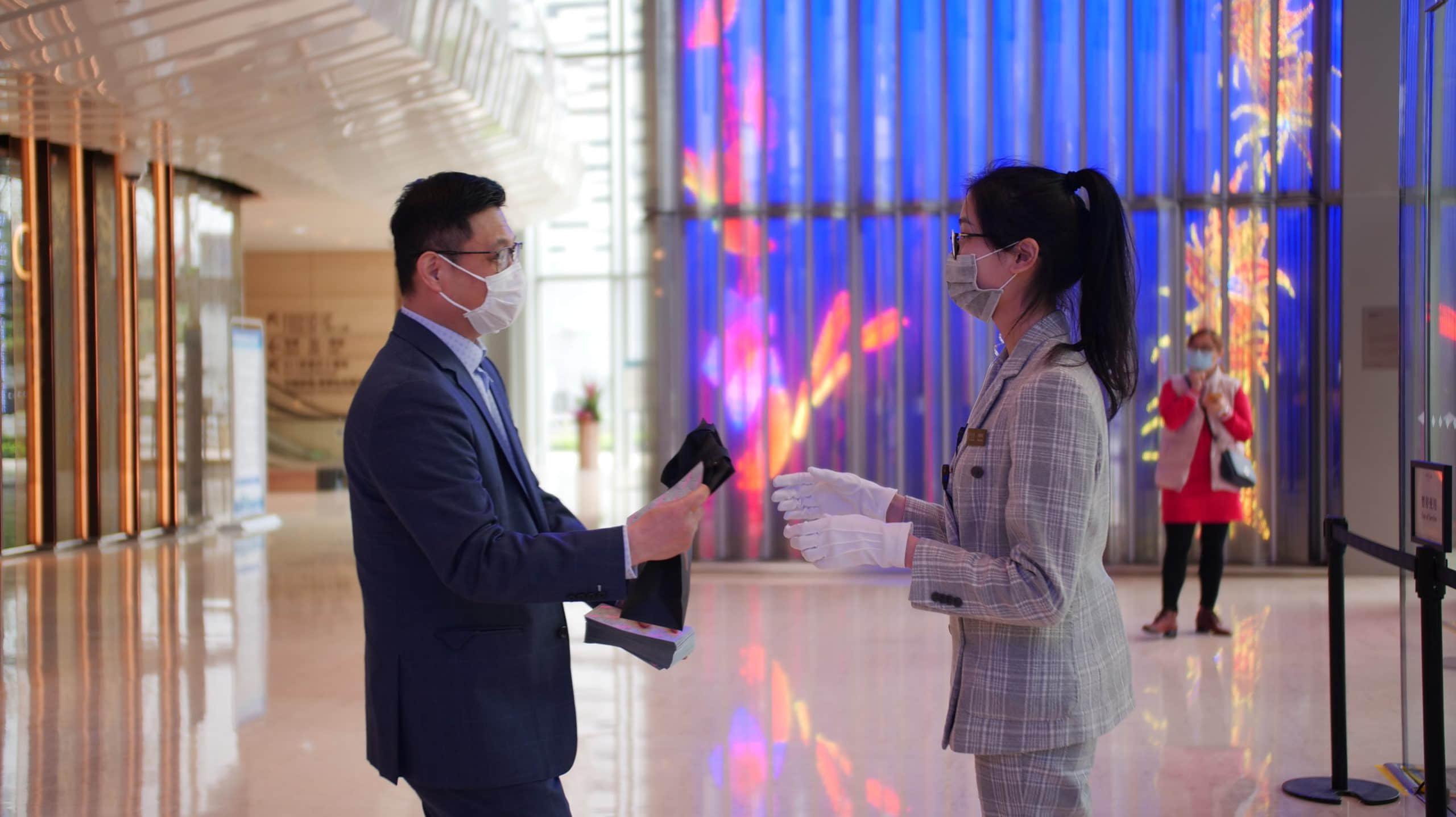 """在广州K11,高级副总裁邹郁(图左)向员工派发""""复工爱心大礼包"""",为他们加油"""